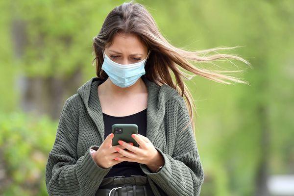 Une jeune femme portant un masque consulte son smartphone - Photo d'illustration