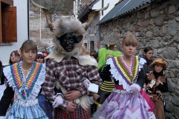"""Carnaval de Bielsa en Aragon. Les deux jeunes """"Madamas"""" aux robes enrubannées, prennent le bras, du """"Trangas"""" mi homme, mi-bouc, au visage recouvert d'huile et de suie."""