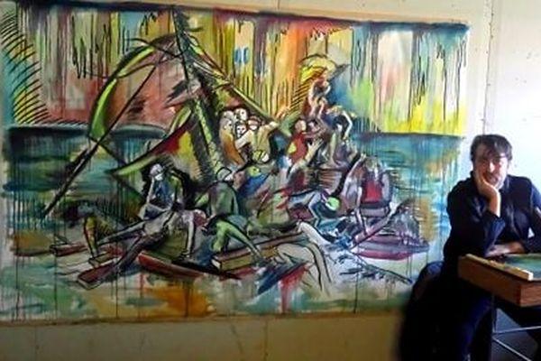 Kim Nezzar devant sa toile. Photo prise par son épouse Stéphanie pour illustrer notre article.