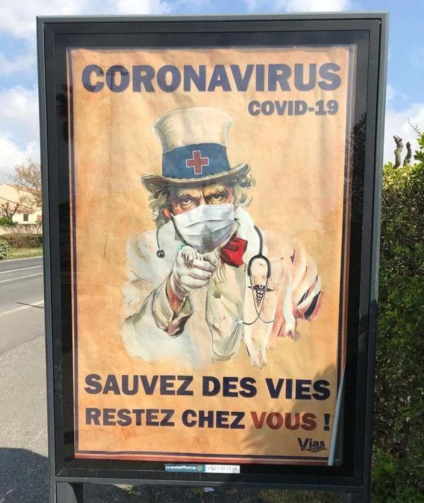 Des affiches de l'Oncle Sam, nez et bouche couverts, à Vias.