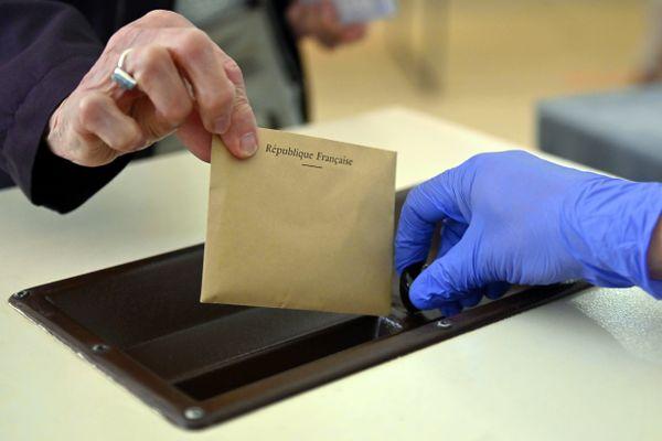 Une femme glisse un bulletin de vote dans l'urne - Photo d'illustration