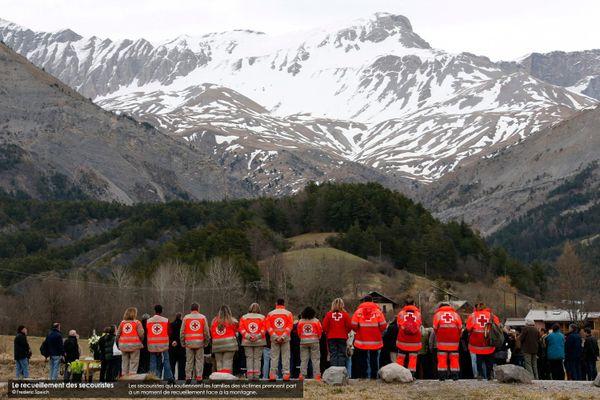Les secouristes qui soutiennent les familles des victimes prennent part à un moment de recueillement face à la montagne.