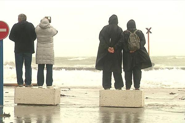 Des promeneurs venus assister au déferlement des vagues sur la digue de Wimereux dimanche.