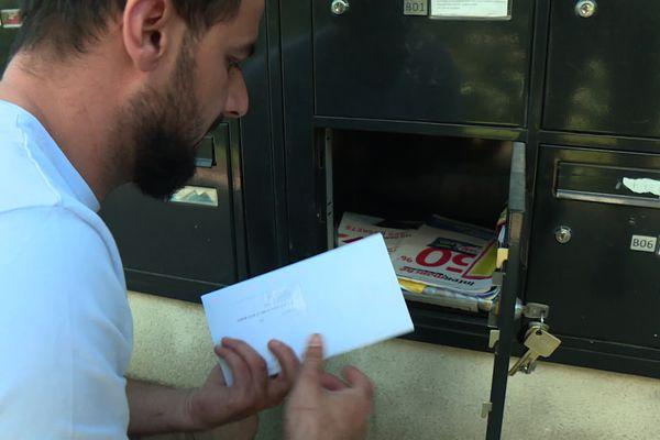 Roméo Vasile devant la boite aux lettres de son premier logement à Toulouse après 15 ans passés dans le bidonville de la Flambère
