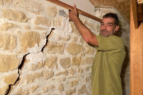 Cet habitant de Saint-Claud (Charente) peut insérer sa main dans la fissure de son mur. Pour autant, sans reconnaissance de l'état de catastrophe naturelle, son assurance ne l'indemnisera pas. et les travaux s'élèvent à 150.000€.