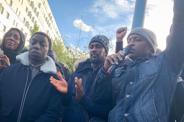 Diané Bah (veste en jeans et bonnet gris), le frère de la victime, prenant la parole lors d'un rassemblement en hommage au jeune Sarcellois au lendemain de sa mort, le 7 octobre dernier (illustration).