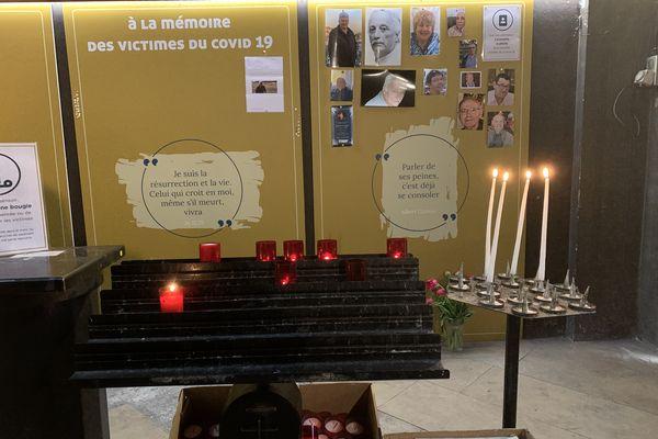 Un mur sur la droite de la chapelle où des photos de victimes sont accrochées. Devant lui, des supports pour déposer une bougie ou un cierge. @Elie SAIKALI / France 3 Paris Île-de-France.
