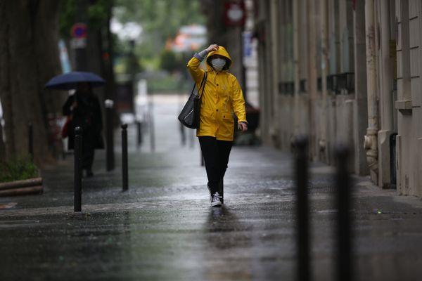 Des piétons portant le masque à Paris, sous la pluie (illustration).