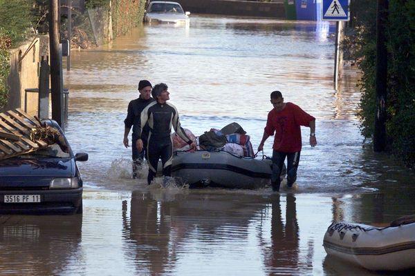 Des sauveteurs parcourent les rues de Cuxac-d'Aude, le 14 novembre 1999, pour aider les personnes sinistrées par les inondations provoquées par les pluies diluviennes des deux jours précédents.