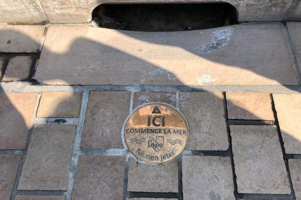"""La ville de Dijon s'équipe de plaques """" Ici commence la mer"""" installées près des bouches d'égout afin d'attirer l'attention des citoyens sur le fait que tout déchet jeté par terre, peut aller polluer la mer et les océans, via les égouts et les cours d'eau."""