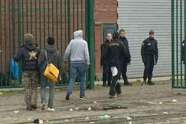 Des migrants sous surveillance policière à Calais.