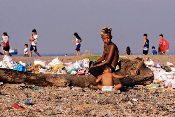 Une plage de Manille où les enfants jouent au milieu des détritus déposés par l'océan.