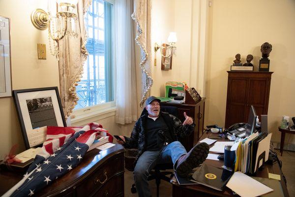 Un supporter de Donald Trump, s'asseyant au bureau de Nancy Pelosi, présidente démocrate de la Chambre des représentants.