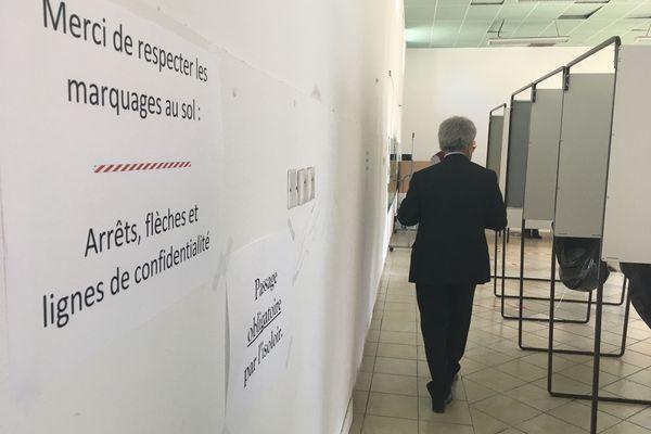 Ange Santini se rend das l'isoloir, dont les rideaux ont été retirés, et tournés vers le mur, pour respecter la discrétion requise.