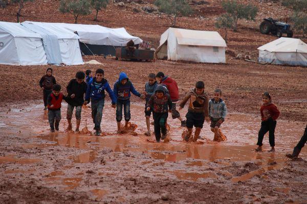(Illustration). Des enfants pataugent dans la boue d'un camp de la province d'Idlib, dans le nord de la Syrie le 5 décembre 2019.