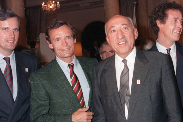 Michel Barnier, alors député de Savoie, Jean-Claude Killy, triple champion olympique à Grenoble en 1968, Henri Dujol, maire d'Albertville, et Guy Drut, assistant à la mairie de Paris en charge des sports, réagissent à l'annonce du CIO le 17 octobre 1986 à Lausanne.