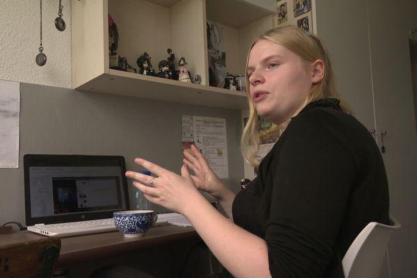 Léna travaille sur son ordinateur dans sa chambre de 9m2