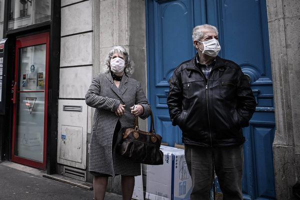 Un couple de personnes âgées portant des masques pour se protéger du nouveau coronavirus, dans les rues de Paris.