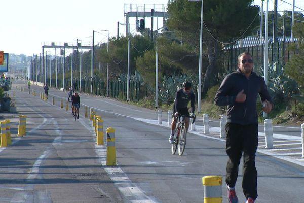 Des coureurs et des cyclistes sur le bord de mer d'Antibes, dans les Alpes-Maritimes.