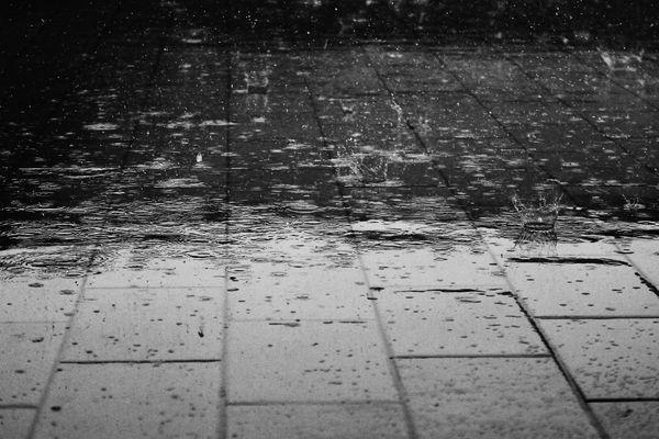 La pluie qui tombe sur un trottoir.