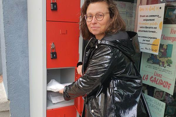 """Sandrine Lebreton, gérante de la librairie """"Point virgule"""", à Aurillac, dans le Cantal, a installé des casiers pour vendre des livres à ses clients pendant le confinement lié au coronavirus COVID 19."""