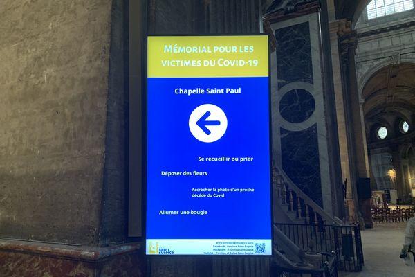 Panneau à l'entrée de l'église Saint-Sulpice indiquant l'emplacement de la chapelle où se trouve le mémorial pour les victimes de la Covid-19. @Elie SAIKALI / France 3 Paris Île-de-France.