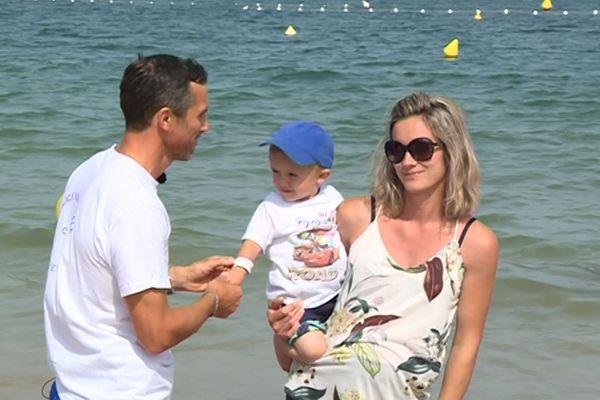 Le policier, ici sur une plage de Saint Jean de Luz, explique à l'enfant et ses parent à quoi doit servir ce bracelet.
