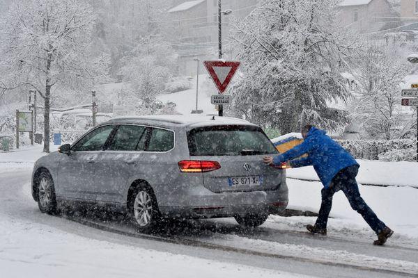 Dans la région de Saint-Etienne, un automobiliste pousse sa voiture sous la neige