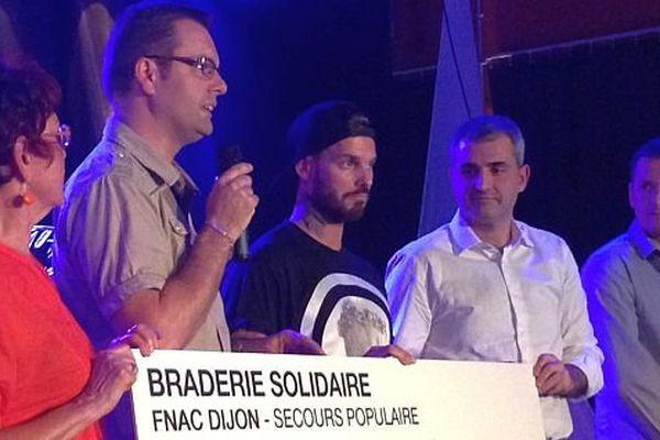 M'Pokora remet un chèque au Secours Populaire, fruit de la braderie solidaire de la FNAC qui a eu lieu il y a une dizaine de jours au Zénith de Dijon.