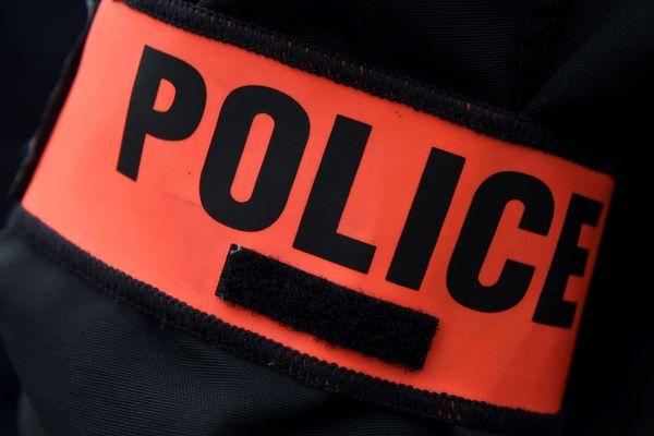 """Un policier en civil pour un brassard avec l'inscription """"Police"""" à son bras"""