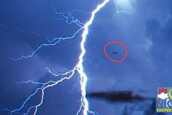 Un avion au décollage, à quelques kilomètres d'un spectaculaire éclair.