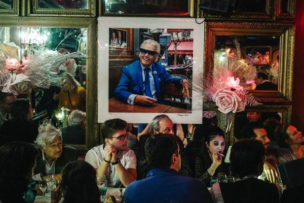 Des clients assis sous le portrait de Michou, le 26 janvier dernier, jour de sa mort.