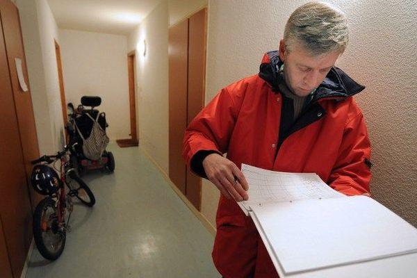 Un agent recenseur compulse ses listings le 21 janvier 2010 dans la cage d'escalier d'un immeuble de Rennes