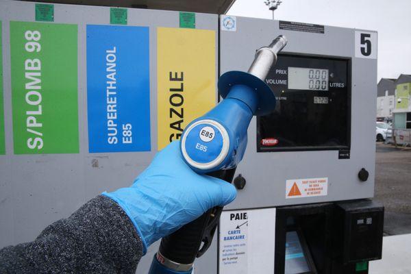 Automobiliste s'apprêtant à mettre du carburant E85 dans le réservoir de sa voiture à une station-service vendant du bioéthanol.