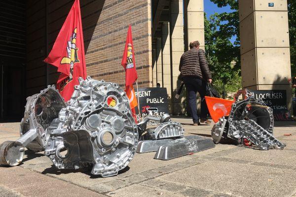 Les salariés de la fonderie MBF de Saint-Claude (Jura) se sont déplacés devant le tribunal de commerce de Dijon avec une partie de leur production, des pièces pour les constructeurs automobiles français.