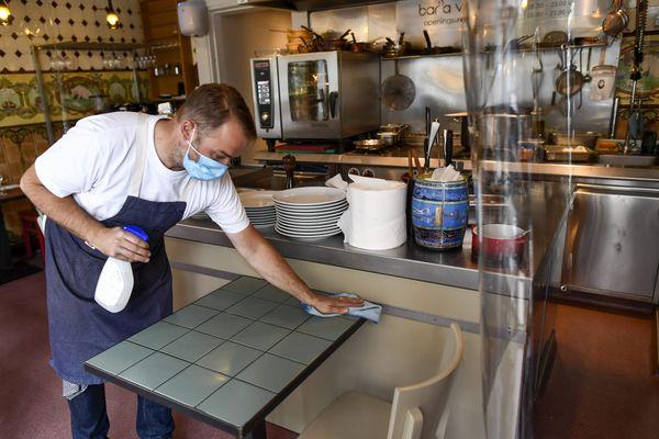 Un restaurateur nettoie ses tables - Photo d'illustration