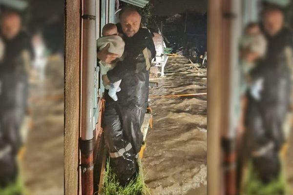 Ce pompier porte un bébé dans ces bras sous la pluie et l'eau du fleuve qui déborde.
