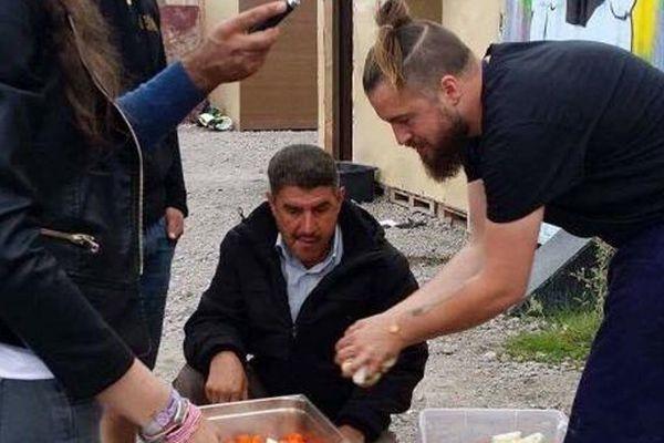 Florent Ladeyn distribue les repas qu'il a préparé avec les migrants.