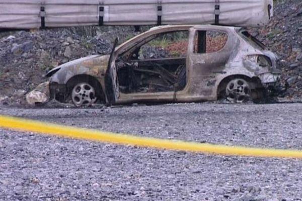 Derrière le camion, dans la zone artisanale, on distingue la carcasse carbonisée de la voiture, une 206 blanche.