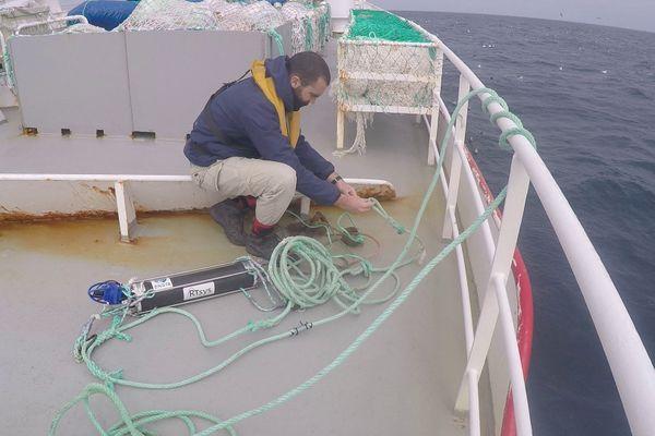 Gaëtan Richard manipule un hydrophone, un microphone pour écouter les sons sous-marins.