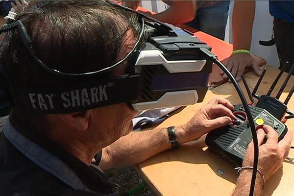 Manette en mains, lunettes de réalité virtuelle sur la tête pour piloter son drone.
