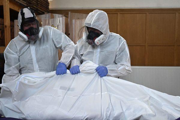 Les services de pompes funèbres prenant en charge le corps d'une personne décédée du Covid-19, à Londres, le 20 avril.