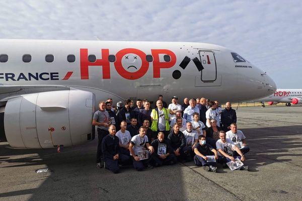 Mobilisation des salariés du site de maintenance de Hop! ce mardi à l'aéroport de Lille-Lesquin. Dans leurs mains, des photos de leurs familles pour dénoncer les conséquences humaines de la fermeture.