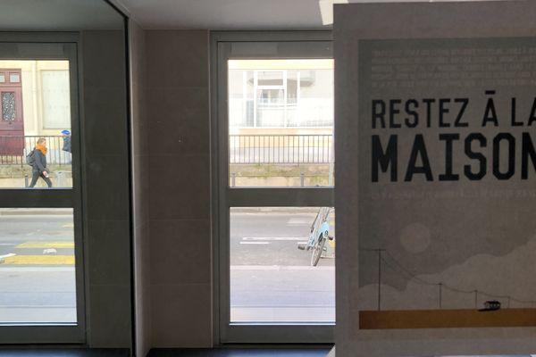 """L'affiche devenue célèbre """"Restez à la maison"""" de Mathieu Persan dans un hall d'immeuble à Paris"""