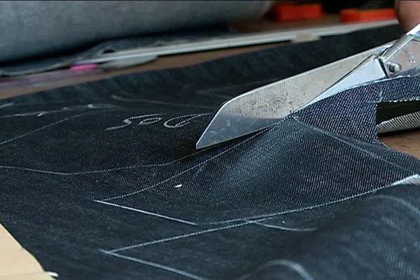 Un pantalon sur mesure découpé dans une toile indigo japonaise, à Toulouse, dans l'atelier de la marque Champ de Manoeuvres