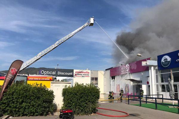 """Les pompiers tentent d'éteindre l'incendie qui a pris sur le toit du magasin """"Autour de Bébé"""" ce samedi matin vers 10h00."""