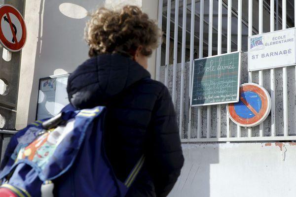 """Devant l'école primaire de Saint Barnabé dans le 12ème arrondissement de Marseille, où la directrice a installé un panneau """"école fermée""""."""