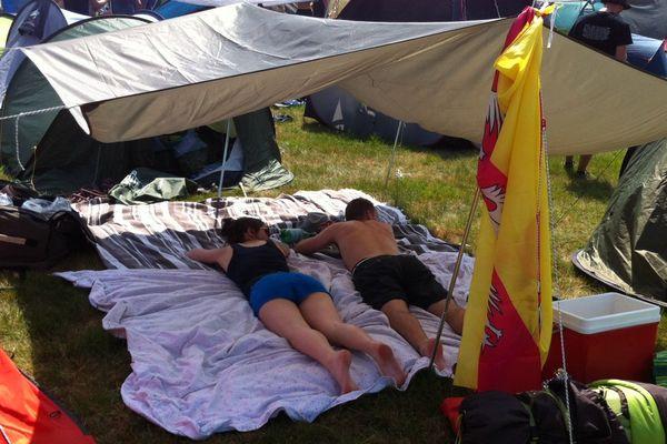 vendredi midi, deux festivaliers font la sieste à l'ombre d'une toile.