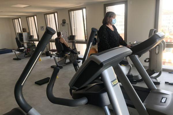 Dans la salle de sport de l'hôpital de jour, les patients sont accompagnés par un enseignant en activité physique adaptée.