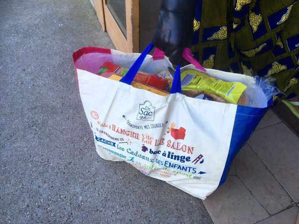Une dame récupère le sac de courses que lui a préparé Youssef Maiza à partir des dons des particuliers.